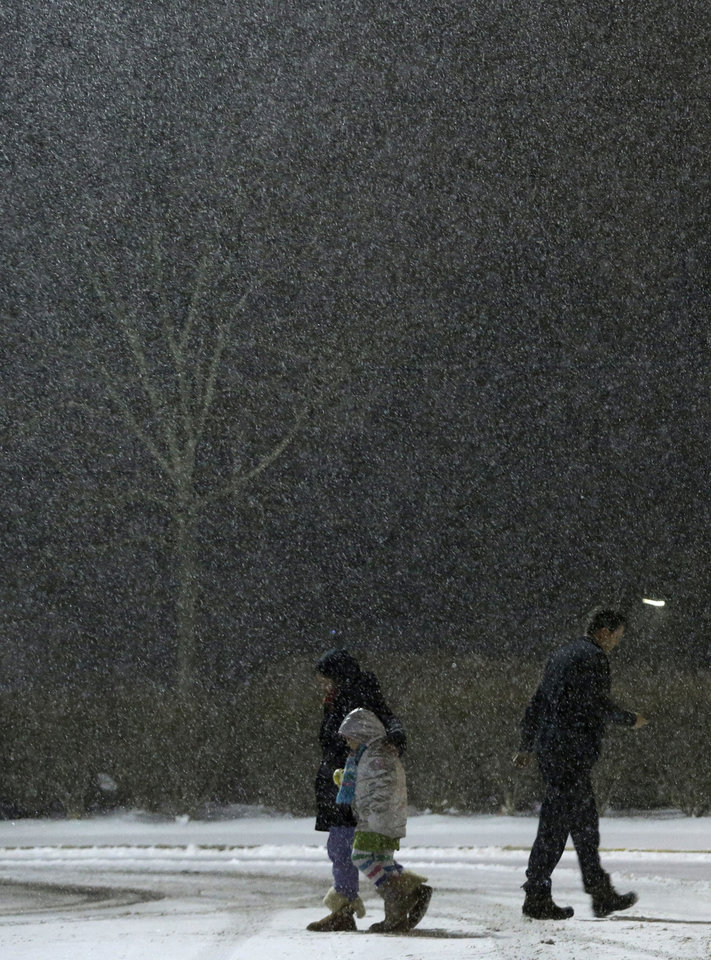 Photo - People walk outside of a store under heavy snow, Thursday, Jan. 2, 2014, in Fairfield, N.J. Snow and bone-chilling temperatures are expected for the overnight hours with substantial accumulation predicted. (AP Photo/Julio Cortez)