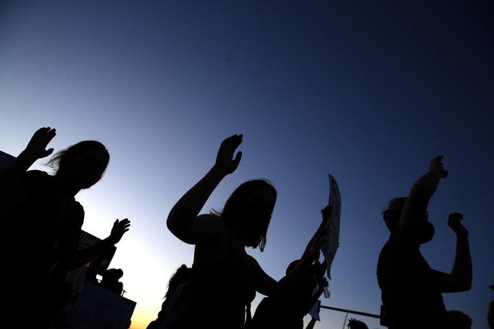 Photo - Protestor raise their arms in the air during a protest near the intersection of 23rd and Classen in Oklahoma City, Saturday, May 30, 2020. The protest was in response to the death of George Floyd. [Sarah Phipps/The Oklahoman]