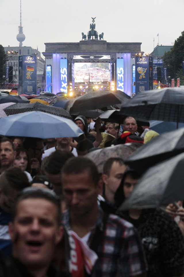 Photo - During heavy rain, thousands of German soccer fans wait for the live broadcast of the final match  between Germany and Argentina at the soccer World Cup in Rio de Janeiro, Brazil,  at a public viewing area called 'Fan Mile' in front of the Brandenburg Gate in Berlin, Sunday, July 13, 2014. (AP Photo/Markus Schreiber)