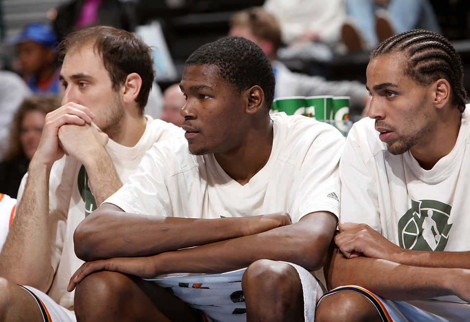 Photo - Oklahoma City's Nenad Krstic, Kevin Durant and Thabo Sefolosha (from left) watch from the bench as the Thunder lose to Indiana during the NBA basketball game between the Indiana Pacers and the Oklahoma City Thunder at the Ford Center in Oklahoma City, Sunday, April 5, 2009.  The Thunder lost 117 to 99. Photo by John Clanton, The Oklahoman ORG XMIT: KOD