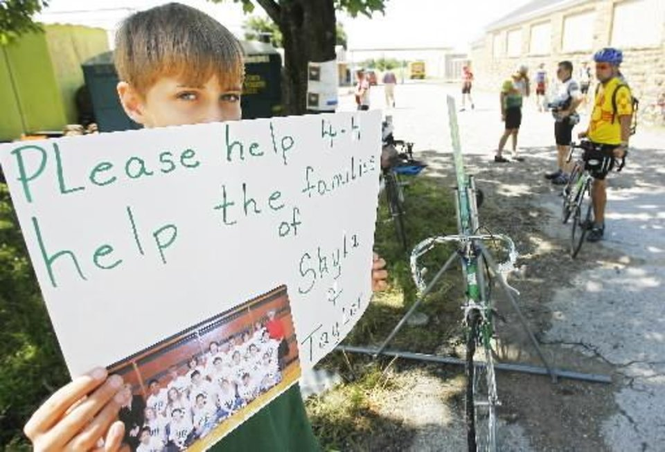 Photo - Bryan Smith, 11, holds a sign requesting donations from the Oklahoma FreeWheel Cross State Bike Tour to help the family of Taylor Paschal-Placker and Skyla Whitaker, who were shot and killed last Sunday on the dirt road near one of their homes. Photo by David McDaniel