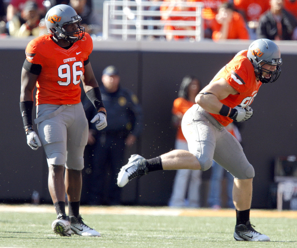Photo - Oklahoma State's Ryan Robinson (96)and Cooper Bassett (80) celebrate a sack during a college football game between the Oklahoma State University Cowboys (OSU) and the Baylor University Bears (BU) at Boone Pickens Stadium in Stillwater, Okla., Saturday, Oct. 29, 2011. Photo by Sarah Phipps, The Oklahoman