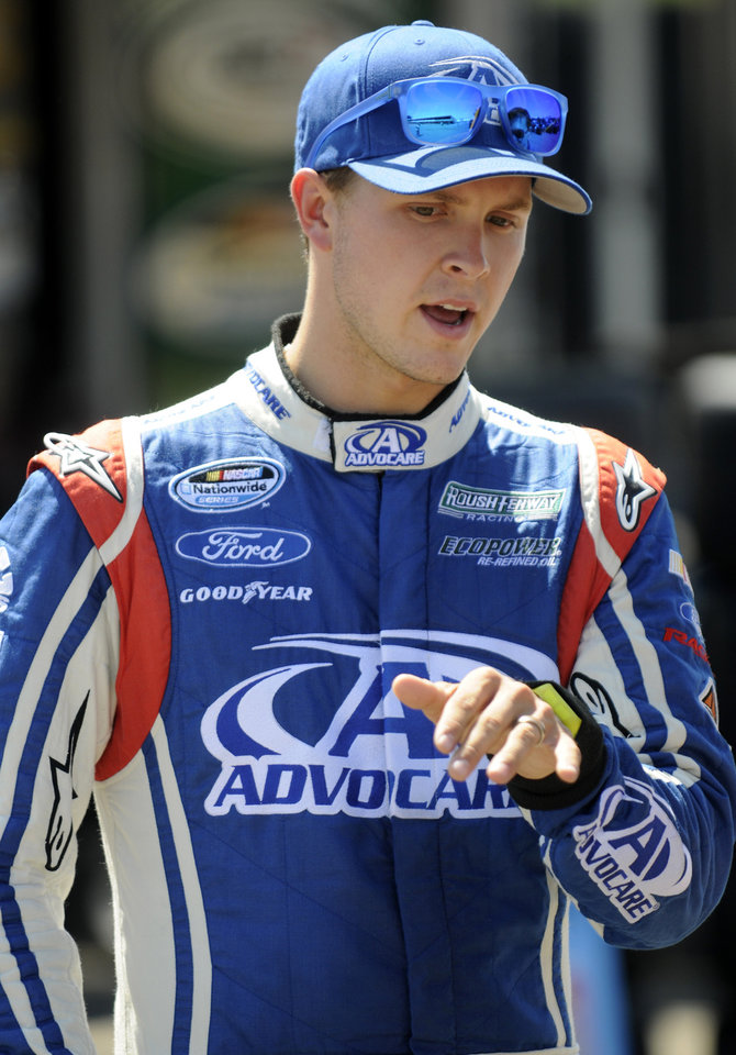 Photo - Trevor Bayne gestures in the garage during practice for the NASCAR Nationwide Series Nationwide Children's Hospital 200 auto race at Mid-Ohio Sports Car Course Friday, Aug. 15, 2014 in Lexington, Ohio. (AP Photo/Tom E. Puskar)