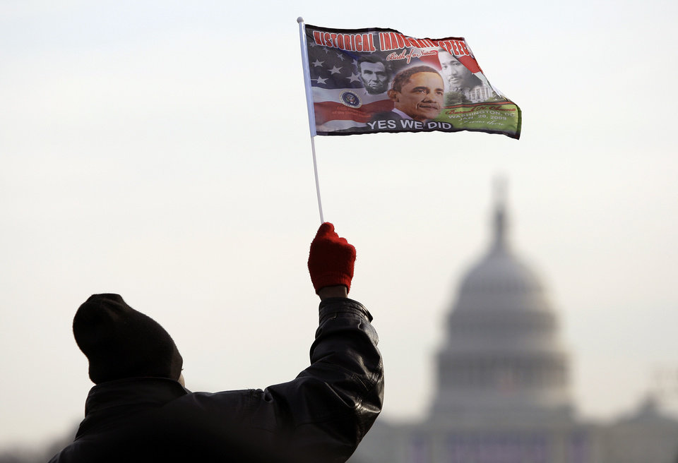 Photo - Das Stoked of Providence, R. I., waves a flag with the image of  President-elect Barack Obama on the National Mall looking towards the U.S. Capitol in Washington, Tuesday, Jan. 20, 2009. (AP Photo/Carolyn Kaster)