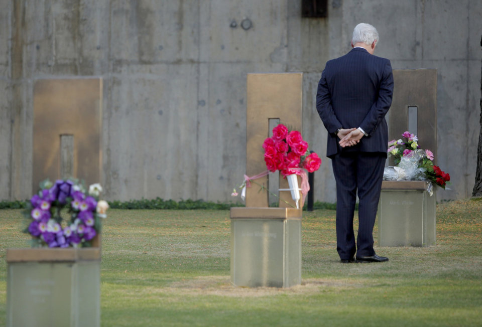 Photo - Former President Bill Clinton stands at the chair of Oklahoma City bombing victim Alan G. Whicher after lying a flowers on the chair during a visit to the Oklahoma City National Memorial & Museum on Wednesday, April 21, 2010. Clinton is in town to receive the Reflections of Hope Award for his work in Oklahoma City after the bombing of the Alfred P. Murrah Federal Building.  Photo by Bryan Terry, The Oklahoman