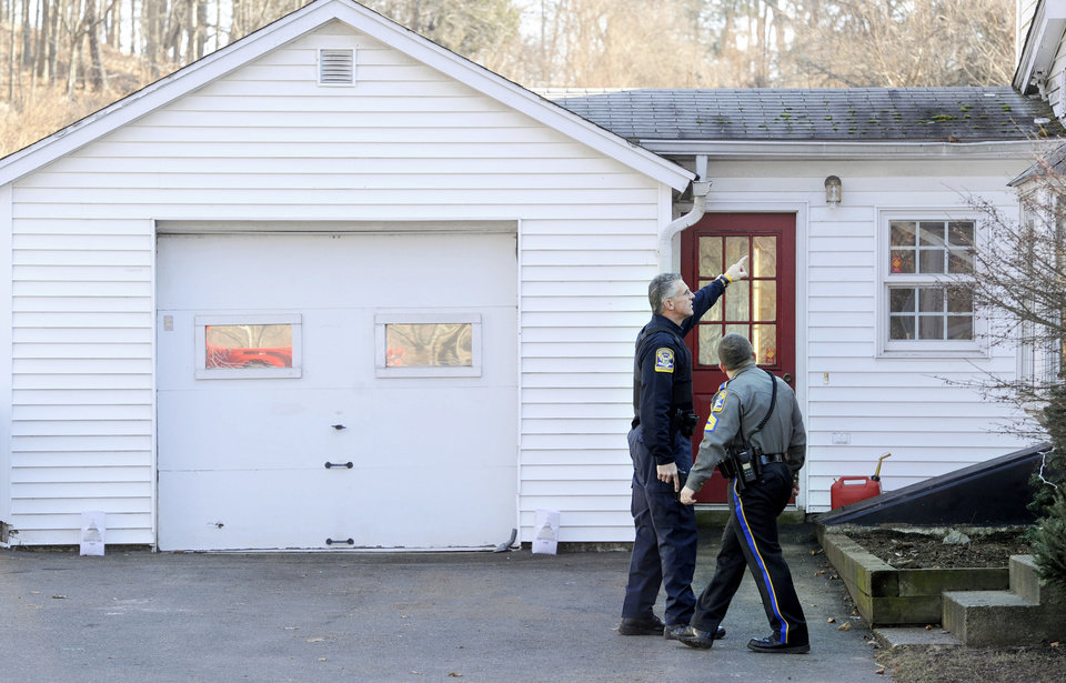 Photo - Law enforcement canvass an area nearby a school shooting at Sandy Hook Elementary School in Newtown, Conn. where authorities say a gunman opened fire, leaving 27 people dead, including 20 children, Friday, Dec. 14, 2012. (AP Photo/Jessica Hill) ORG XMIT: CTJH111