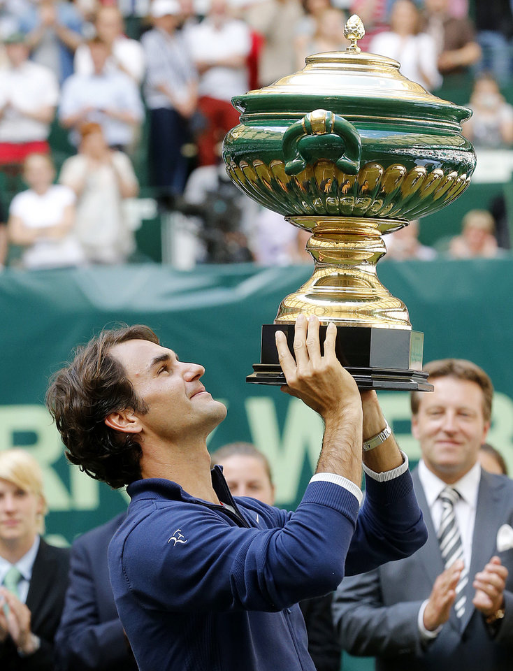 Photo - Switzerland's Roger Federer lifts the trophy after winning the final of the Gerry Weber Open tennis tournament in Halle, Germany, Sunday, June 15, 2014. Federer beat Colombia's Alejandro Falla 7-6 and 7-6. (AP Photo/Michael Probst)