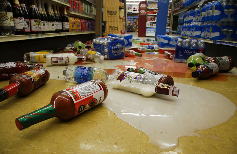 Photo - Bottles lay spilled on the ground in White's Foodliner grocery store in Pawnee after a 5.6 magnitude earthquake, Sat. Sept. 3, 2016. JESSIE WARDARSKI/Tulsa World