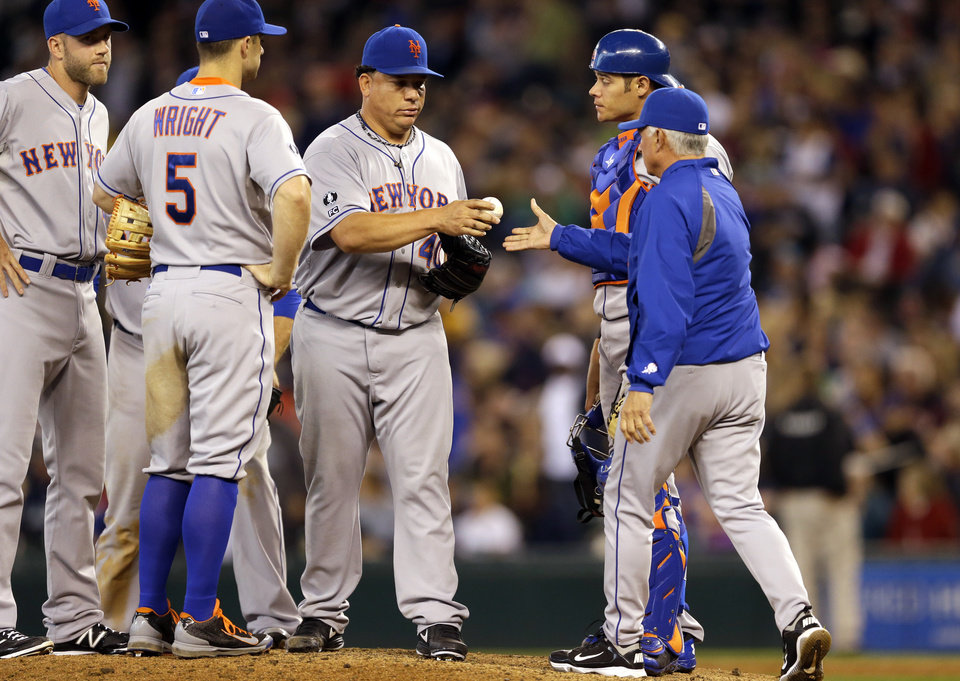 Photo - New York Mets starting pitcher Bartolo Colon, third from right, is pulled in the eighth inning by manager Terry Collins, front right, during a baseball game against the Seattle Mariners, Wednesday, July 23, 2014, in Seattle. The Mets won 3-2. (AP Photo)