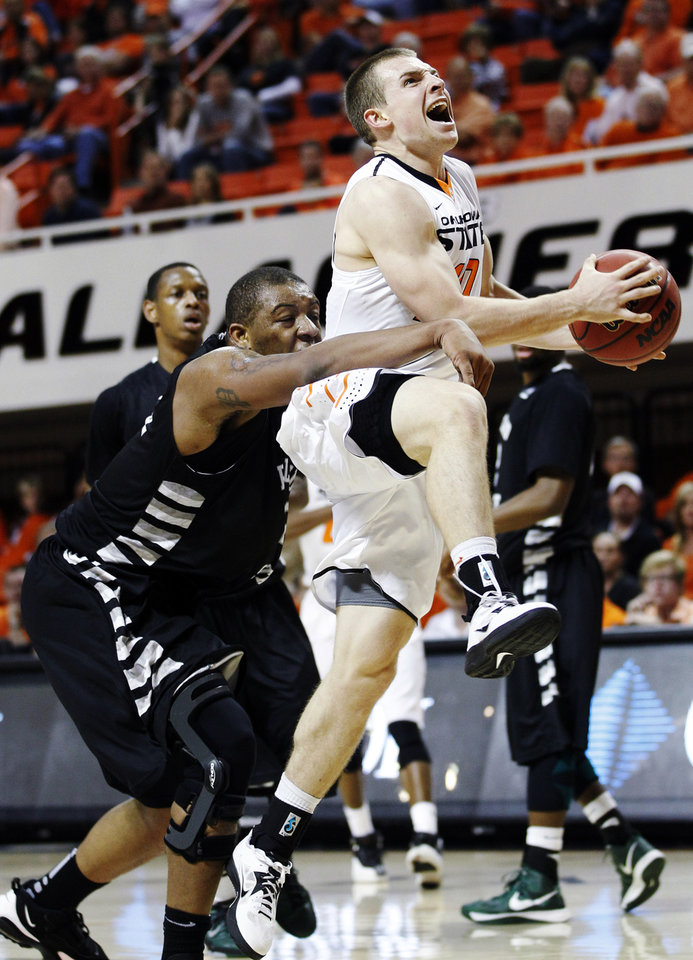 Photo -   Oklahoma State guard Phil Forte, right, is fouled by Portland State center Lamont Prosser, left, in the second half of an NCAA college basketball game in Stillwater, Okla., Sunday, Nov. 25, 2012. Oklahoma State won 81-58. (AP Photo/Sue Ogrocki)
