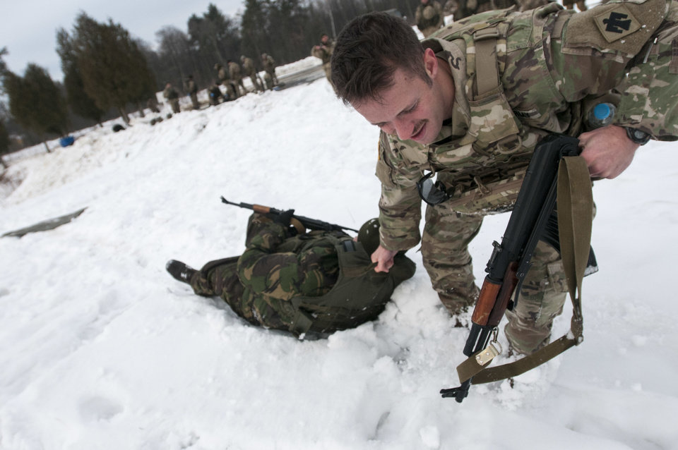 Photo -  Sgt. Carey Bennett, of Oklahoma City, drags a Ukrainian soldier through snow to demonstrate evacuating a casualty during a Ukrainian-led combat first aid course in February at the International Peacekeeping and Security Center, near Yavoriv, Ukraine. [Photo by Sgt. Anthony Jones, 45th Infantry Brigade Combat Team]