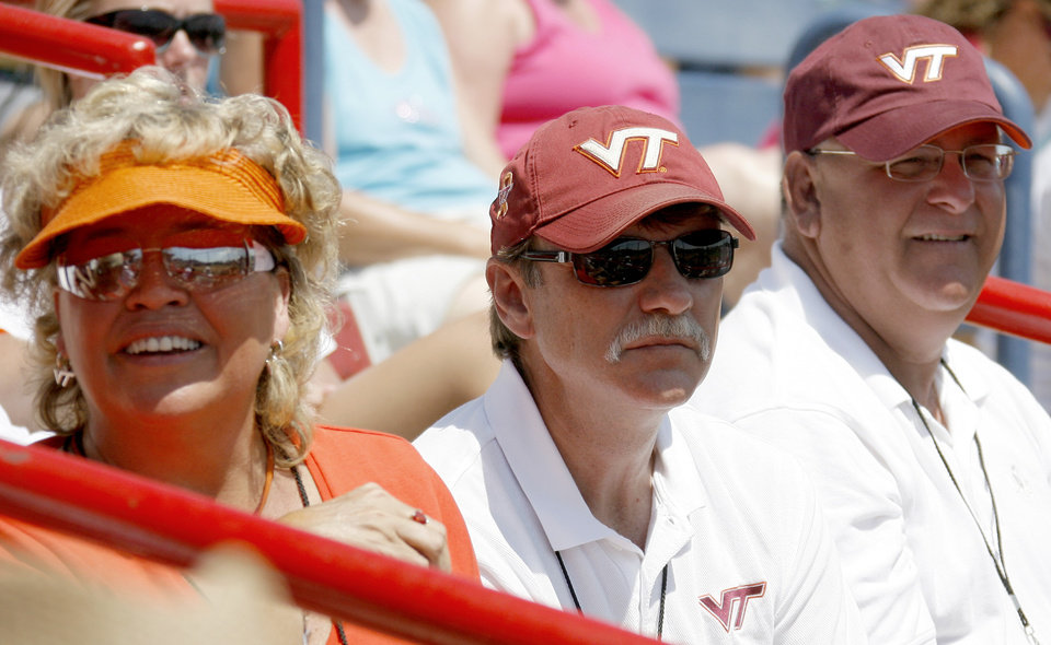 Photo - Julie Denney, left, Denny Tincher, and Rusty Denney watch during the Women's College World Series game between Florida and Virginia Tech at ASA Hall of Fame Stadium in Oklahoma City, Saturday, May 31, 2008. BY BRYAN TERRY, THE OKLAHOMAN