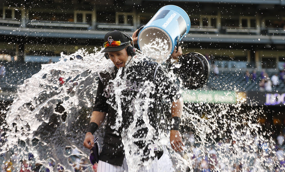 Photo - Colorado Rockies' Drew Stubbs, front, reacts after being doused by teammates Brandon Barnes as Stubbs is interviewed after hitting a three-run, walkoff home run against the Cincinnati Reds in the ninth inning of a baseball game in Denver on Sunday, Aug. 17, 2014. The Rockies won 10-9.(AP Photo/David Zalubowski)
