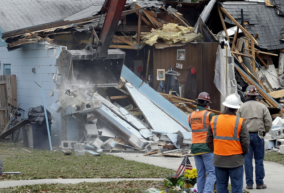 Photo - Demolition experts watch as the home of Jeff Bush, 37,  is destroyed Sunday, March 3, 2013, in Seffner, Fla. The 20-foot-wide opening of the sinkhole was almost covered by the house, and rescuers said there were no signs of life since the hole opened Thursday night. (AP Photo/Chris O'Meara)