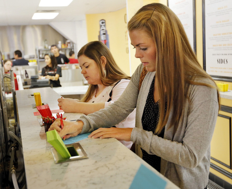 Photo - Brittni Slattery , right, and Aimee Canavan  fill out order forms at the new Cafe 7 inside the First National Center on Wednesday in downtown Oklahoma City. Photos by Nate Billings, The Oklahoman