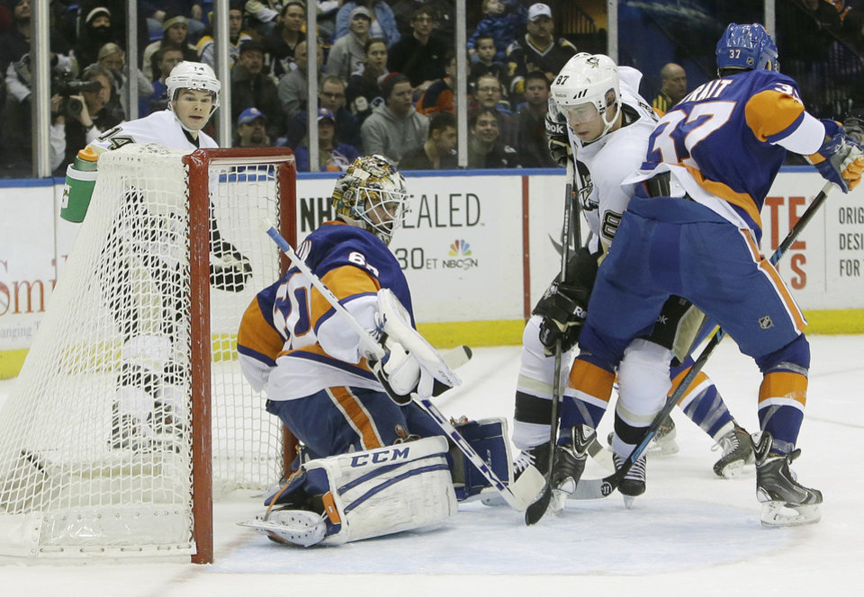 Photo - Pittsburgh Penguins' Sidney Crosby (87) shoots the puck past New York Islanders goalie Kevin Poulin (60) during the first period of an NHL hockey game Thursday, Jan. 23, 2014, in Uniondale, N.Y. (AP Photo/Frank Franklin II)