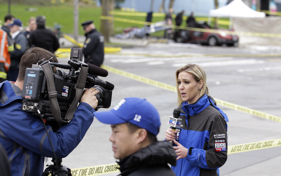 Photo - KOMO broadcaster Kelly Koopmans, right, works at the scene of the crash of a KOMO news helicopter Tuesday, March 18, 2014, in Seattle.  The helicopter helicopter crashed into a city street near Seattle's Space Needle on Tuesday, killing two people and critically injuring a person in a car on the ground. (AP Photo/Stephen Brashear)