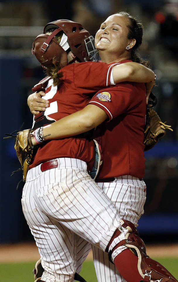 Photo - Alabama pitcher Jaclyn Traina (33), right, hugs catcher Molly Fichtner (22) after Game 6 of the Women's College World Series softball tournament between Alabama and Kentucky at ASA Hall of Fame Stadium in Oklahoma City, Friday, May 30, 2014. Alabama won, 2-0. Photo by Nate Billings, The Oklahoman