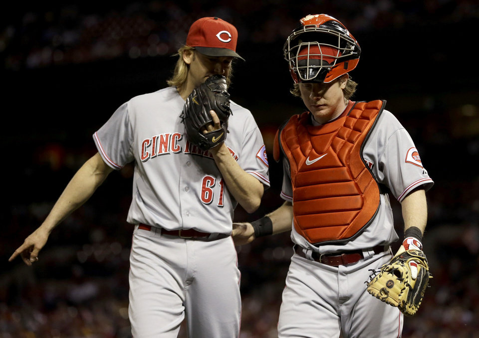 Photo -   Cincinnati Reds starting pitcher Bronson Arroyo, left, and catcher Ryan Hanigan walk off the field after working the second inning of a baseball game against the St. Louis Cardinals, Monday, Oct. 1, 2012, in St. Louis. (AP Photo/Jeff Roberson)