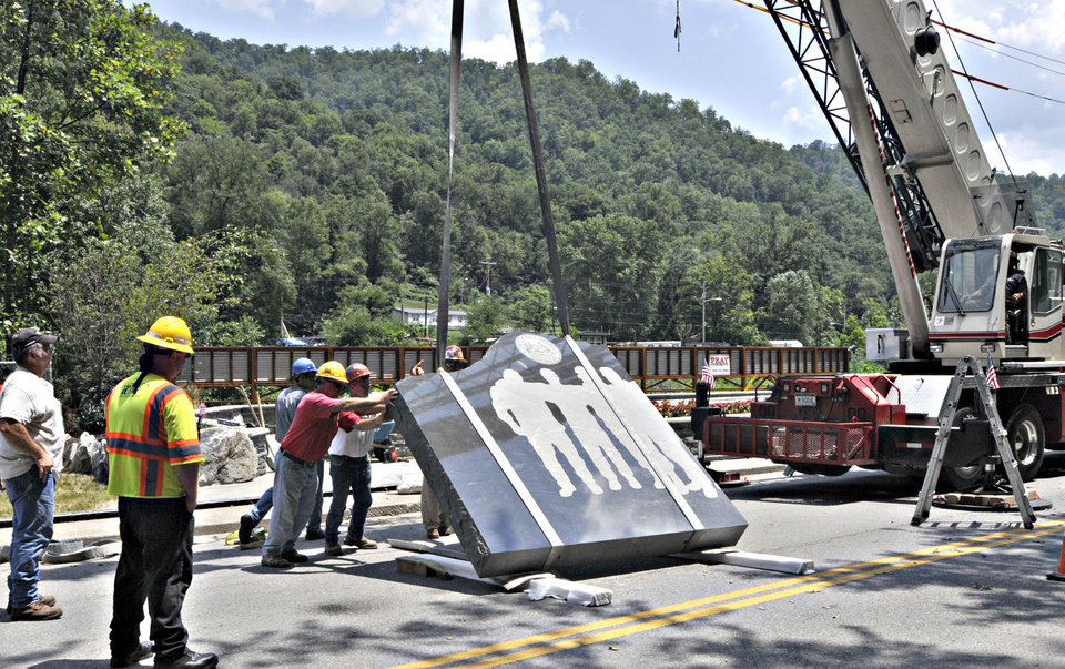 Photo -   Workers line up the first piece of granite on the base of the UBB Memorial in Whitesville, W.Va., Tuesday July 17, 2012. Silhouettes of the 29 miners are on one side of the slabs and a history of coal mining in West Virginia is on the other side. (AP Photo/The Charleston Daily Mail, Tom Hindman)