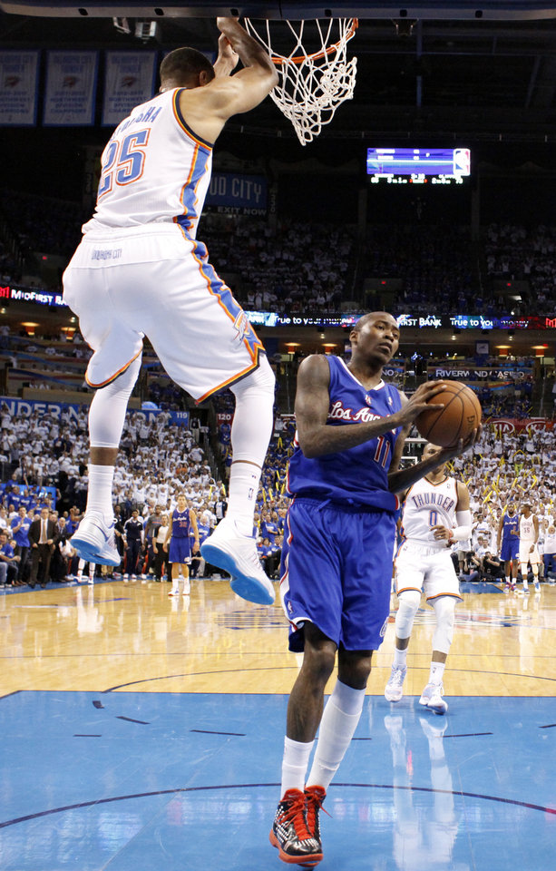 Photo - Los Angeles' Jamal Crawford (11) reacts as Oklahoma City's Thabo Sefolosha (25) hangs on the rim after a dunk during Game 2 of the Western Conference semifinals in the NBA playoffs between the Oklahoma City Thunder and the Los Angeles Clippers at Chesapeake Energy Arena in Oklahoma City, Thursday, May 8, 2014. Photo by Sarah Phipps, The Oklahoman