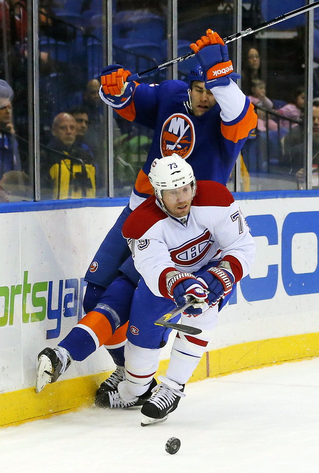 Montreal Canadiens right wing Michael Ryder (73) checks New York Islanders defenseman Joe Finley (52) and steals the puck in the first period of an NHL hockey game at the Nassau Coliseum in Uniondale, N.Y., Tuesday, March 5, 2013. (AP Photo/Paul J. Bereswill)