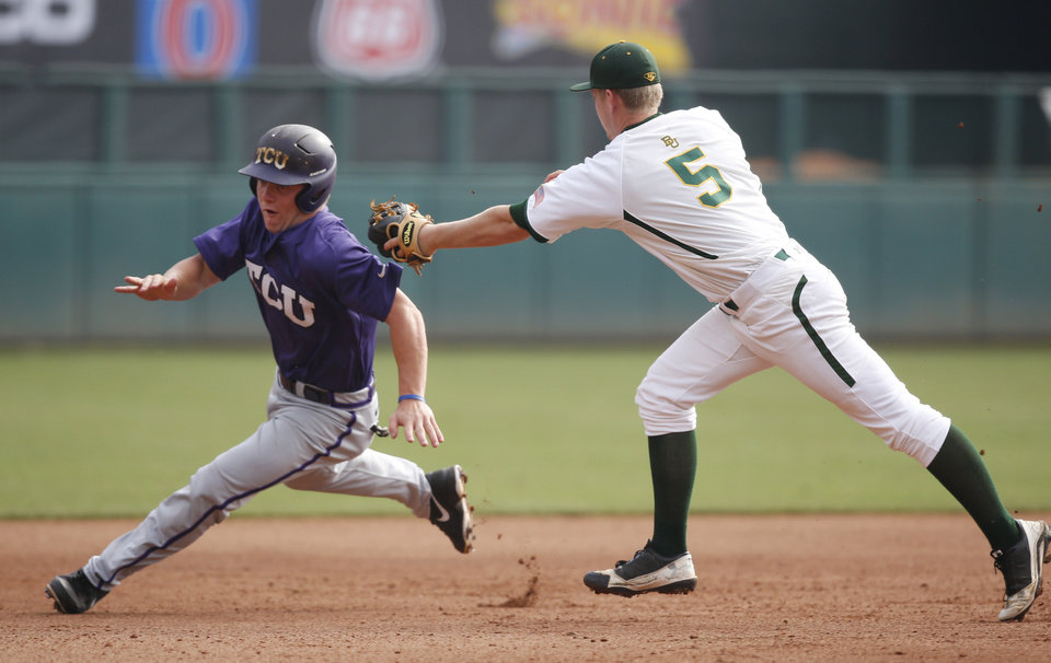 Photo - TCU's Boomer White, left, evades the tag of Baylor third baseman Duncan Wendel (5) in the first inning of a game during the Big 12 conference NCAA college baseball tournament in Oklahoma City, Saturday, May 24, 2014. White slid past the base and was successfully tagged out by Wendel on the second attempt. (AP Photo/Sue Ogrocki)