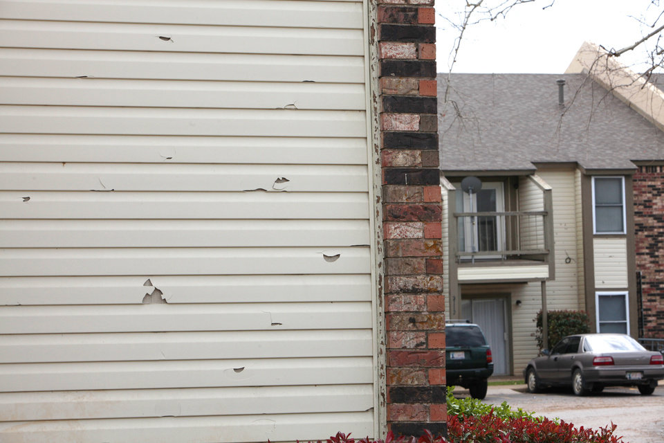 Siding at Quorum Condominiums shows hail damage.