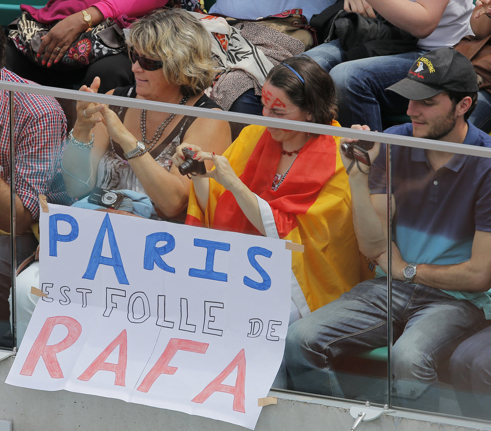 Photo - Tennis fans, one draped in the Spanish flag, sit next to a sign reading