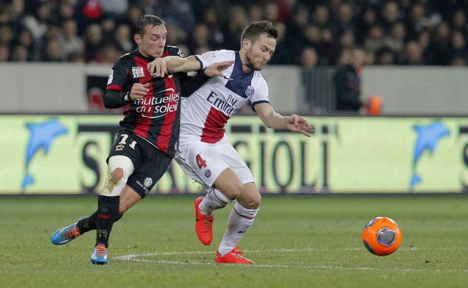 Photo - Nice's Eric Bautheac of France, left, challenges Paris Saint Germain's Yohan Cabaye of France for the ball during their French League One soccer match, in Nice stadium,southeastern France, Friday, March 28, 2014. (AP Photo/Lionel Cironneau)
