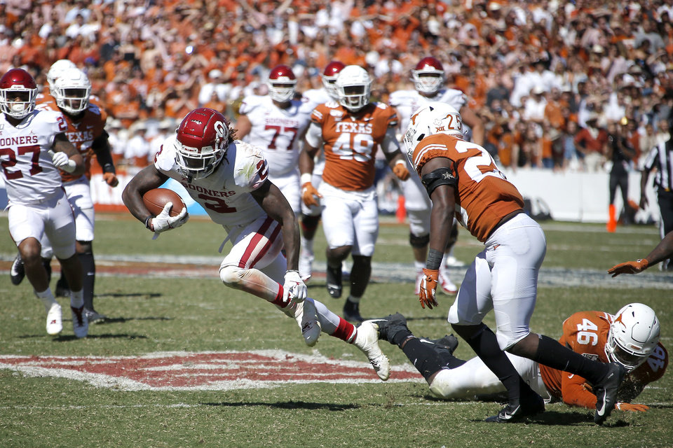 Photo - Oklahoma wide receiver CeeDee Lamb (2) runs past Texas defensive back B.J. Foster (25), and linebacker Joseph Ossai (46) on his way to the end zone during the Red River Showdown college football game between the University of Oklahoma Sooners (OU) and the Texas Longhorns (UT) at Cotton Bowl Stadium in Dallas, Saturday, Oct. 12, 2019. Oklahoma won 34-27. [Bryan Terry/The Oklahoman]