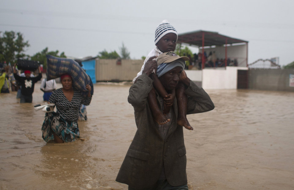 Photo -   A man carries a child as residents leave an area flooded by Tropical Storm Isaac in Port-au-Prince, Haiti, Saturday, Aug. 25, 2012. Tropical Storm Isaac swept across Haiti's southern peninsula early Saturday, dousing a capital city prone to flooding and adding to the misery of a poor nation still trying to recover from the 2010 earthquake. (AP Photo/Dieu Nalio Chery)