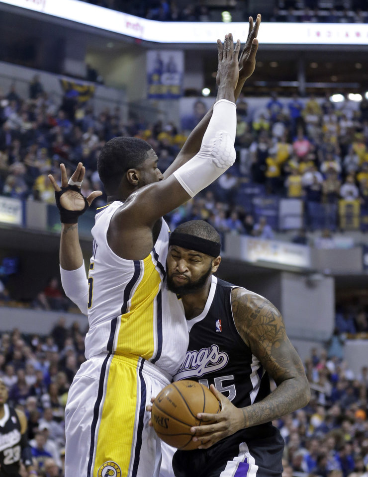 Photo - Sacramento Kings center DeMarcus Cousins, right, crashes into Indiana Pacers center Roy Hibbert in the first half of an NBA basketball game in Indianapolis, Tuesday, Jan. 14, 2014. (AP Photo/Michael Conroy)