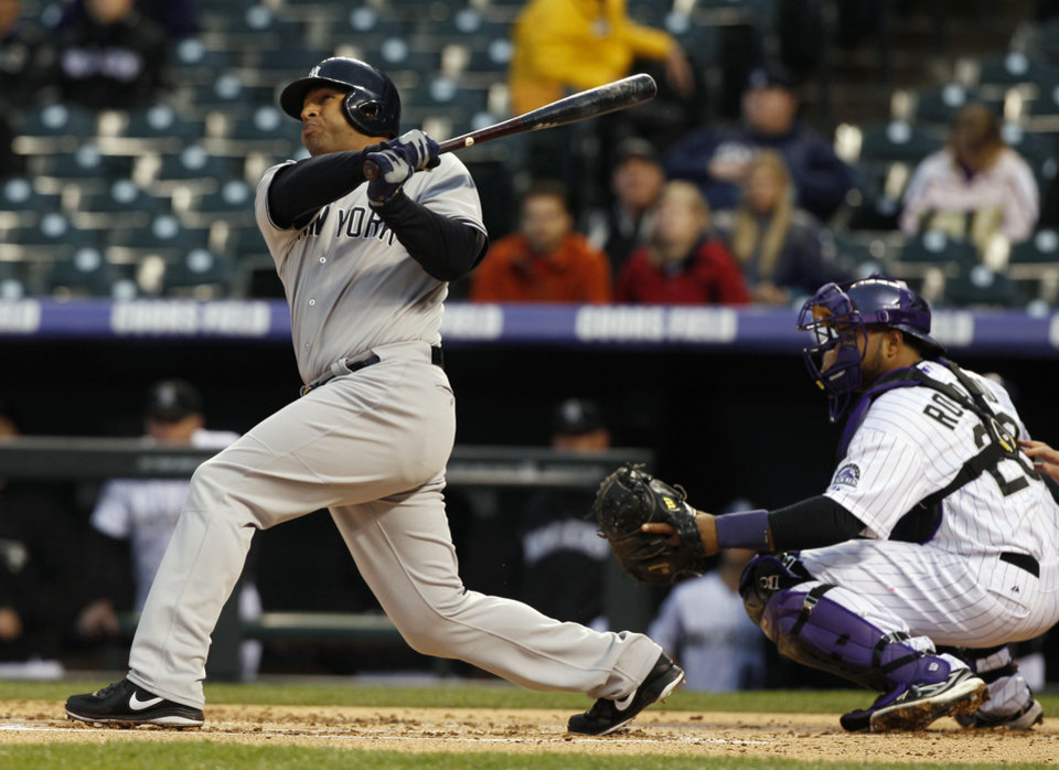 Photo - New York Yankees' Vernon Wells, left, follows the flight of his two-run home run with Colorado Rockies catcher Wilin Rosario in the first inning of a baseball game in Denver on Wednesday, May 8, 2013. (AP Photo/David Zalubowski)