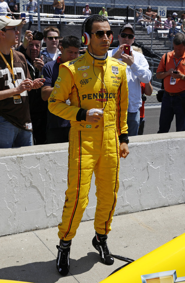 Photo - Helio Castroneves, of Brazil, listens to music as he waits for his turn to qualify for the Indianapolis 500 IndyCar auto race at the Indianapolis Motor Speedway in Indianapolis, Sunday, May 18, 2014. (AP Photo/Tom Strattman)