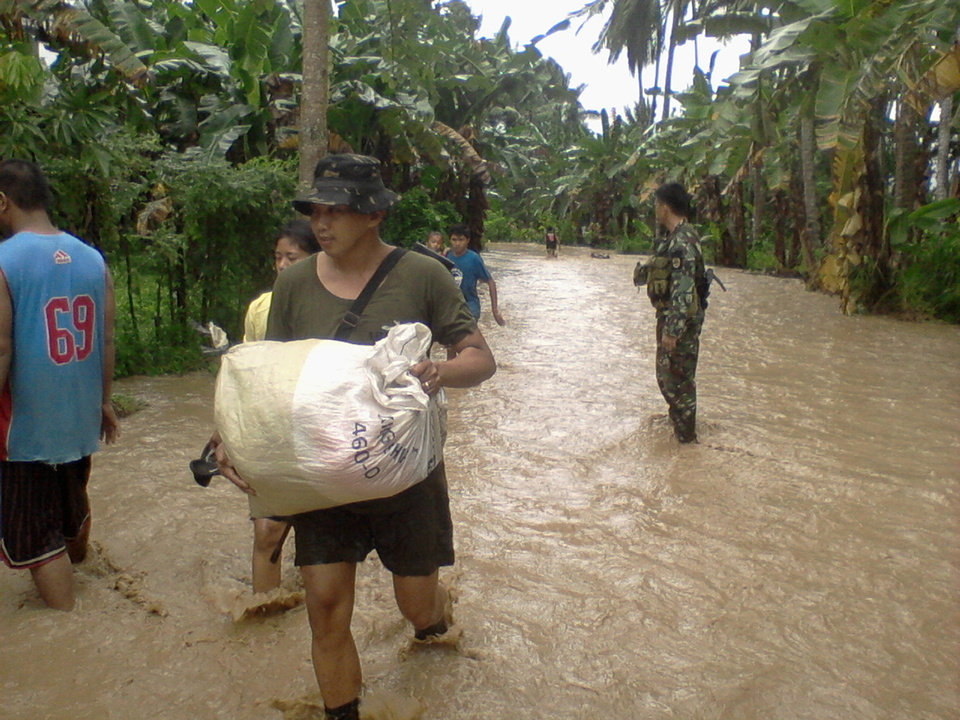 Photo - In this photo taken Tuesday, Dec. 4, 2012 and released by the Philippine Army, a soldier of the 71st Infantry Battalion, 1001st Infantry Brigade of the Philippine Army assists a local resident to carry a sack along a flooded area in Compostela Valley, southern Philippines. The death toll from Typhoon Bhopa climbed to more than 100 people Wednesday, Dec. 5, while scores of others remain missing in the worst-hit areas of the southern Philippines. (AP Photo/The Philippine Army) NO SALES