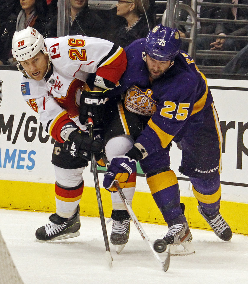 Los Angeles Kings left winger Dustin Penner (25) and Calgary Flames defenseman Dennis Wideman (26) battle for the puck in the second  period of an NHL hockey game in Los Angeles Saturday, March 9, 2013. (AP Photo/Reed Saxon)