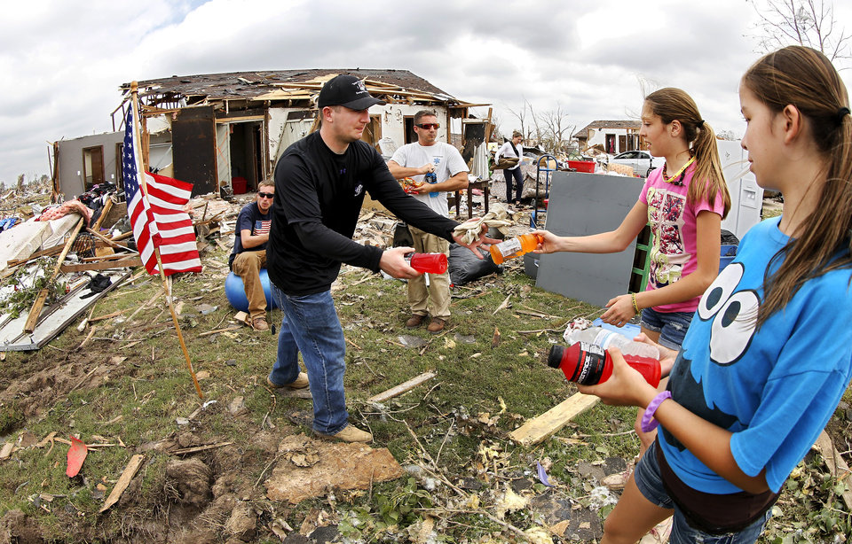 Remi Long and Linda Feagan, far right, give ice cold Gatorade bottles to volunteers. Taking the bottled drink is US Army Capt. Erik Anthes, who drove to Moore with several fellow soldiers from the 1st battalion, 16th infantry regiment at Ft. Riley, KS.  The  girls are part of a  group that came from the north Dallas area to help refresh volunteers. The bed of their truck was filled with cold beverages and light food, including beef jerky. They also brought a trailer loaded with toiletries and gloves to distribute. They are from a small town called Blue Ridge and they said the community  organized a drive earlier in the week requesting donated items for the relief effort. Volunteers from various parts of the country joined Oklahomans in assisting residents on Saturday,  May 25, 2013, doing whatever was needed to remove debris and salvage items from this neighborhood east of Santa Fe, north of SW 19 Street.  An EF5 tornado leveled many neighborhoods in Moore and southwest Oklahoma City last Monday.   Photo  by Jim Beckel, The Oklahoman.