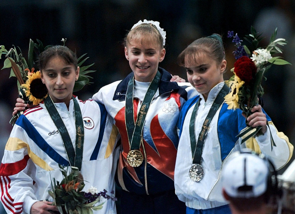 Photo - Gold medalist Shannon Miller, center, of the United States, poses with silver medalist Lilia Podkopayeva, right, and bronze medalist Gina Gogean of Romania during the awards ceremony of the women's individual event gymnastics finals of the Centennial Summer Olympics Games in Atlanta Monday, July 29, 1996. The three gymnasts were the winners on the balance beam. (AP Photo/Susan Ragan)  SUSAN RAGAN - AP - Associated Press