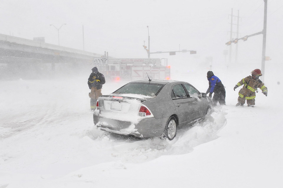 Amarillo emergency personnel assist a stranded motorist on the I-40 service road Monday, Feb. 25, 2013. A blizzard packing 50 mph wind gusts and more than 11 inches of snow blasted Amarillo and Texas Panhandle Monday, Feb. 25, 2013, making travel nearly impossible. Interstate 40 and many major highways in the Panhandle have been closed. (AP Photo/The Amarillo Globe News,Michael Schumacher)
