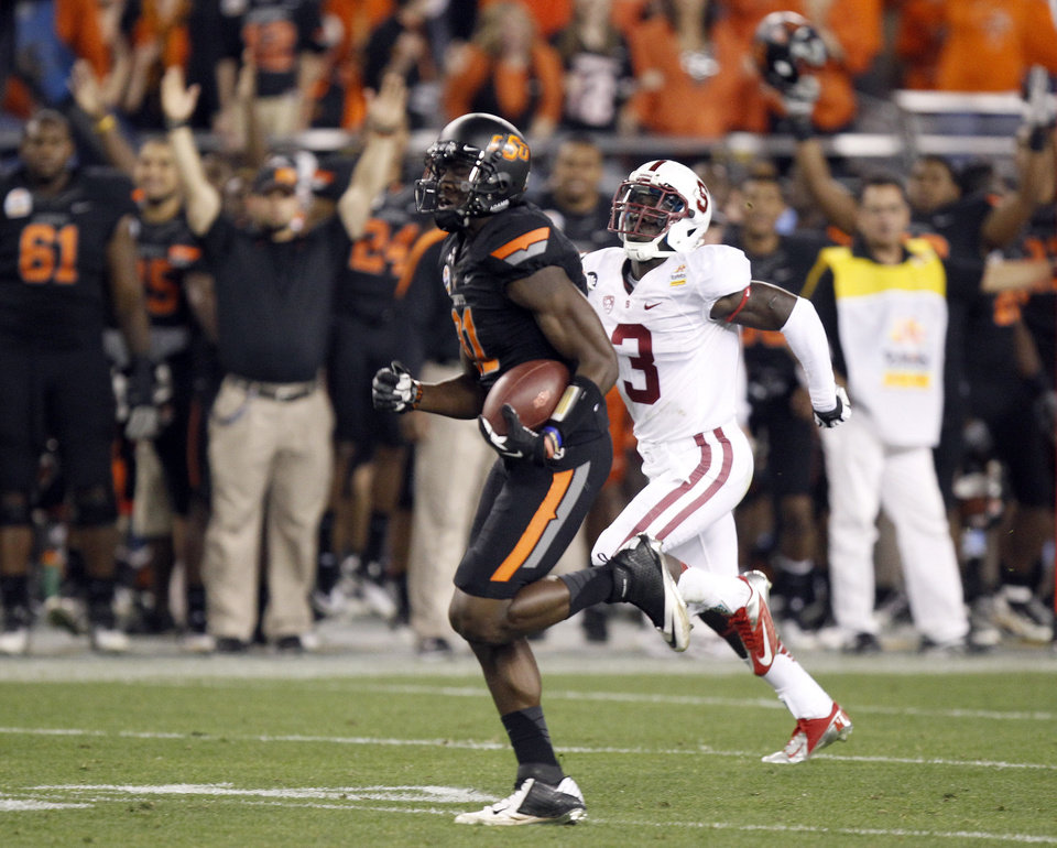 Photo - Oklahoma State wide receiver Justin Blackmon, left, sprints for the end zone for a touchdown after making a reception in front of Stanford safety Michael Thomas, right, during the first half of the Fiesta Bowl NCAA college football game Monday, Jan. 2, 2012, in Glendale, Ariz. (AP Photo/Paul Connors)