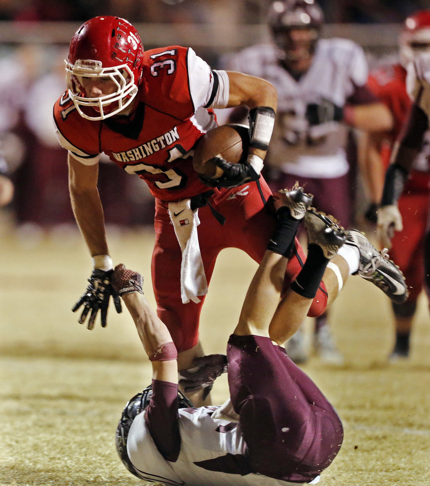 Photo - Washington's Collin Andrews leaps over Ethan Foster as the Nowata Ironmen play the Washington Warriors in high school football on Friday, Nov. 28, 2014 in Washington, Okla. Photo by Steve Sisney, The Oklahoman