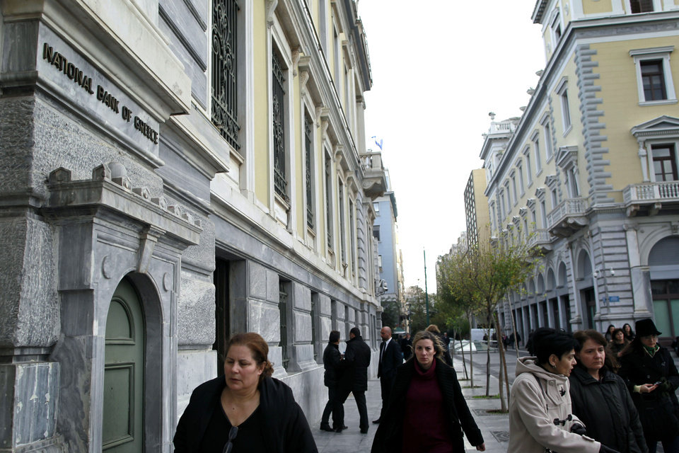 Athenians walk past a central Athens branch of National Bank of Greece, the country\'s largest lender, Tuesday, Dec. 11, 2012. Greece was expected to announce later Tuesday the results of a bond buyback hoped to cut some 20 billion euros off the country\'s 340 billion euro debt load. Domestic lenders will contribute strongly in the European-funded buyback, which if successful will open the way for disbursement of a delayed international rescue loan payment. (AP Photo/Petros Giannakouris)