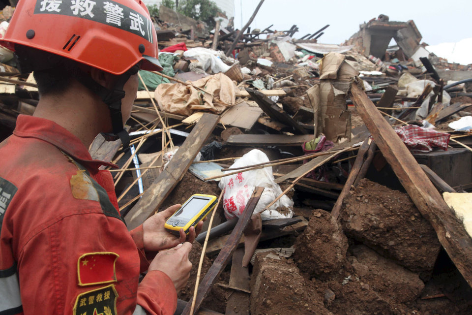 Photo - In this photo released by China's Xinhua News Agency, a rescuer searches for missing people at quake-hit Longquan Village of Longtoushan Town in Ludian County, southwest China's Yunnan Province, Monday. Aug. 4, 2014.  Rescuers dug through shattered homes Monday looking for survivors of the strong earthquake in southern China's Yunnan province that toppled thousands of homes on Sunday, killing hundreds and injuring more than a thousand people.  (AP Photo/Xinhua, Wu Zhangjun) NO SALES