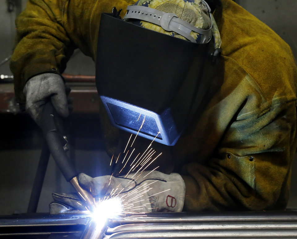 Photo -  An inmate wears protective equipment as he welds.