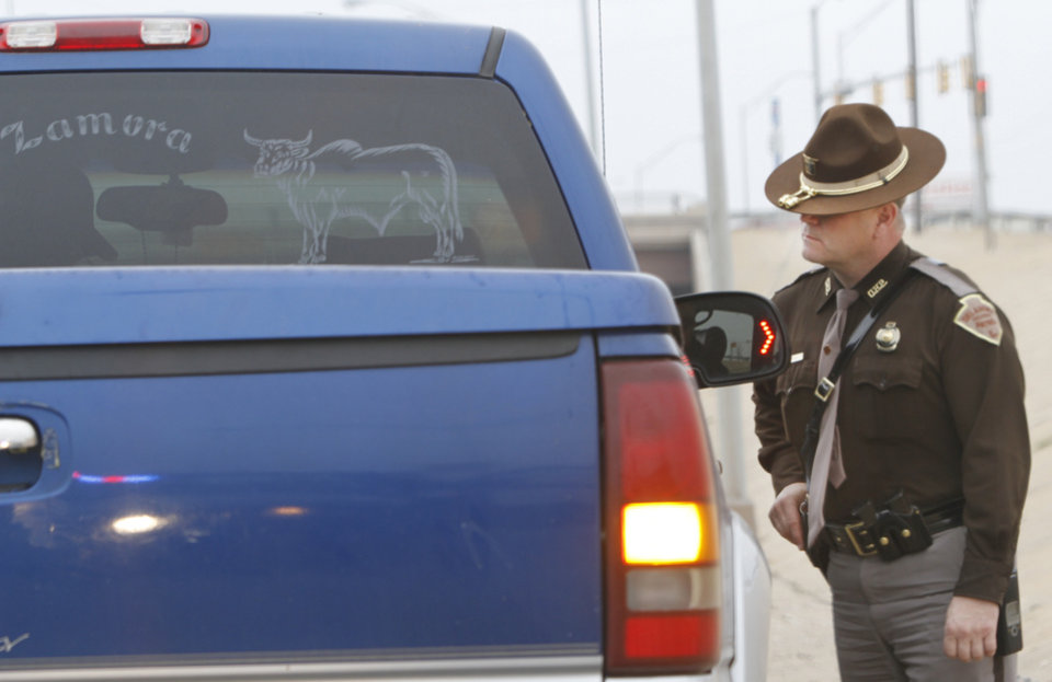 Photo - Oklahoma Highway Patrol trooper Mike Moler talks with a motorist he stopped for speeding Jan. 25 on Interstate 240 in Oklahoma City. Photo By Steve Gooch, The Oklahoman  Steve Gooch