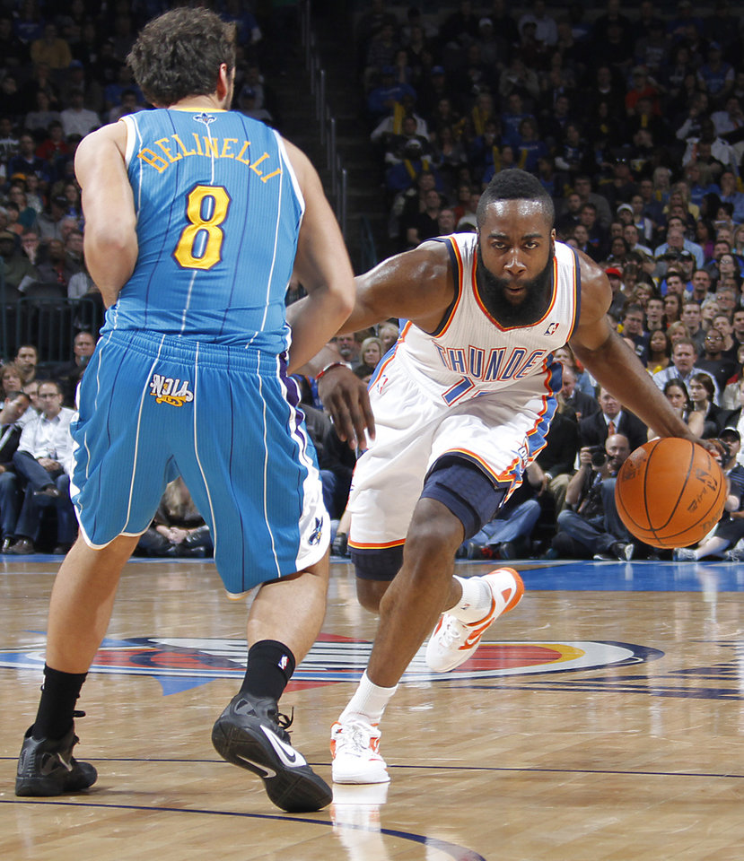 Photo - Oklahoma City Thunder guard James Harden (13) drives past New Orleans Hornets shooting guard Marco Belinelli (8) during the NBA basketball game between the Oklahoma City Thunder and the New Orleans Hornets at the Chesapeake Energy Arena on Wednesday, Jan. 25, 2012, in Oklahoma City, Okla. Photo by Chris Landsberger, The Oklahoman
