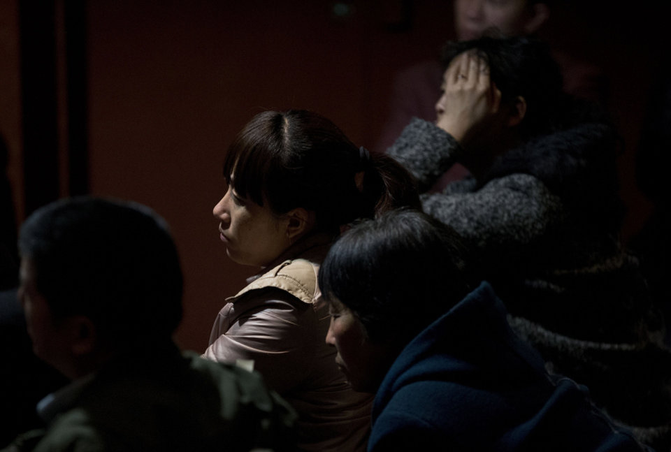 Photo - Relatives of Chinese passengers aboard the missing Malaysia Airlines, MH370 watch a TV news program about the plane at a hotel ballroom in Beijing, China, Thursday, March 20, 2014. Four military search planes were dispatched Thursday to try to determine whether two large objects bobbing in a remote part of the Indian Ocean spotted by satellite imagery were part of a possible debris field of the missing Malaysia Airlines flight. (AP Photo/Andy Wong)