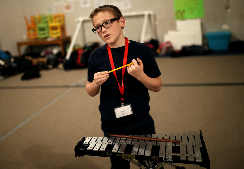 Photo - Percussionist Dane Benson, 9, a fourth grader at Kaiser Elementary School, practices during a recent El Sistema Oklahoma session.   SARAH PHIPPS - The Oklahoman