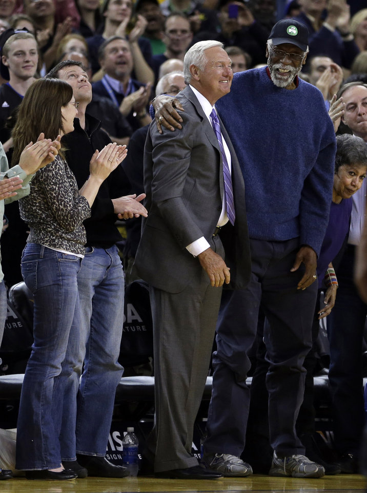 Basketball Hall of Famers Bill Russell, right, and Jerry West acknowledge a standing ovation during the first half of an NBA basketball game between the Golden State Warriors and the Sacramento Kings Wednesday, March 27, 2013, in Oakland, Calif. (AP Photo/Ben Margot)